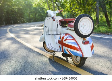 SAKON NAKHON ,THAILAND - JUNE 21 :On June 21,2017,Old vespa in the road forest background travel on holiday