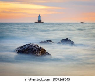 Sakonnet Point lighthouse landscape during golden hour at sunset. The seascape is a long exposure with smooth silky water and rocky foreground.