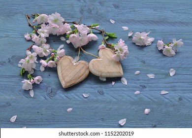 Sakura flowers with hearts on wooden background