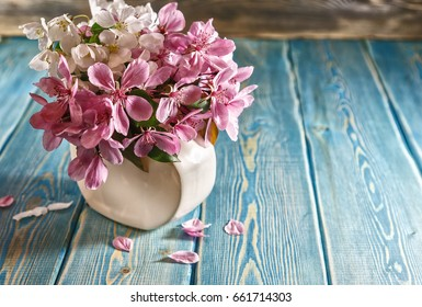 Sakura in vase. Red delicate Japanese flowers in a small vase standing on the table. Table of blue planed boards. Painted surface of the table. The blue color of the boards. Fallen flower petals.