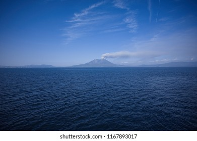 Sakurajima volcano eruption with white ash smoke at crater on the island, Kagoshima Prefecture, Kyushu, Japan. Captured from Cargo Ship in sea