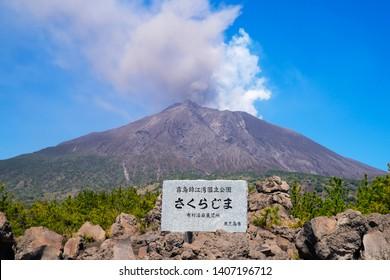 "Sakurajima volcano view from Arimura lava observatory, Kagoshima city, Japan Stone sign indicates place name, ""Sakurajima volcano"", National park name, ""Arimura observatory""and""Kagoshima city"""