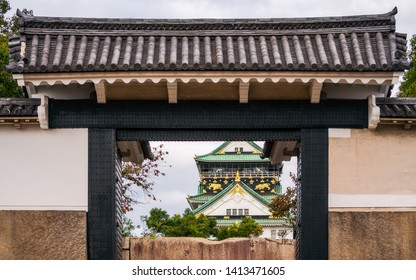 Sakura-mon Gate with Osaka Castle view in the distance in Japan. The iconic symbol of Osaka in the Kansai region of Japan played an important role in the unification of Japan during the samurai era.