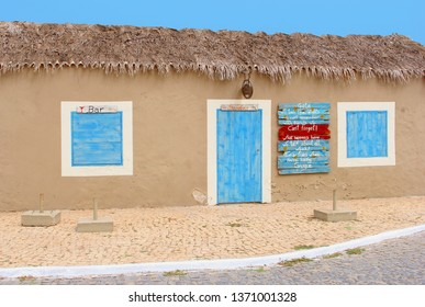 SAL, CAPE VERDE, AFRICA - December 21, 2017. Front view of colorful club bar with roof of palm leaves selling souvenirs,  local Grogue and other alcoholic drinks in fishing village street.
