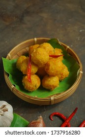 Sala Lauak is an Indonesian fried snack from West Sumatra made from rice flour, salted fish, shallots, garlic, leek, chili sauce & spices & shaped into balls. Street food, rattan bowl, selective focus