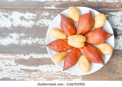 Salacca or salak fruit peeled and not peeled on white plate.