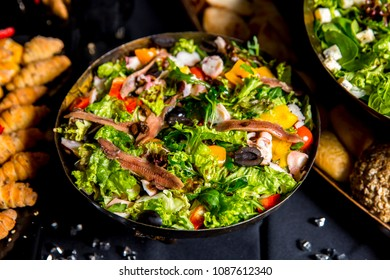 salad with anchovies lettuce, olives, tomatoes, mushrooms and onion on dark background