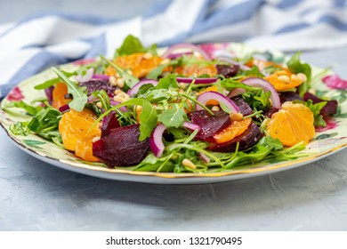 Salad of arugula, baked beetroot, tangerine, red onion and pine nuts in a dish on a textured gray table, selective focus.