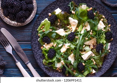 Salad with arugula cheese brie and blackberry