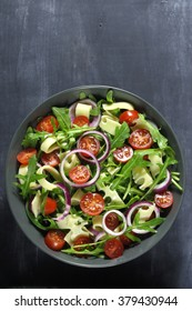 Salad with arugula, cheese, tomato and red onion