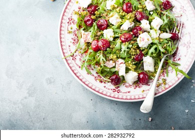 Salad with arugula, cherries and goat cheese on a blue background