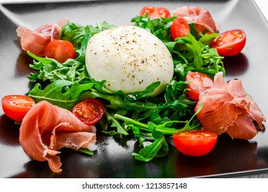 Salad from arugula, egg poached and a hamon on a plate