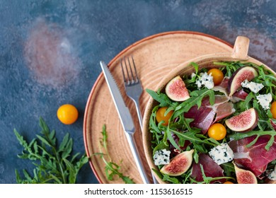 Salad from arugula with figs, jamon, blue cheese and yellow cherry tomatoes
