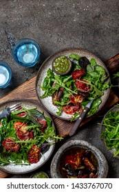 Salad with arugula, spinach, dried tomato and ham serrano paleta iberica. Low carbs keto recipe