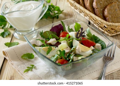 Salad with arugula and spinach, meat and vegetables on a wooden table.