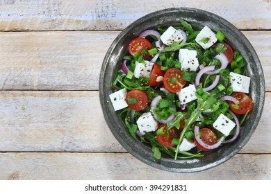 Salad with arugula, tomato, cheese and red onion