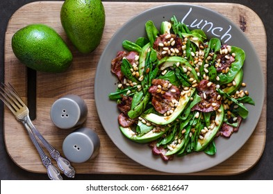 Salad with avocado bacon spinach and pine nuts with balsamic cream