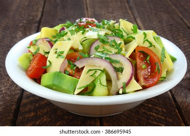 Salad with avocado, cheese, tomato and red onion