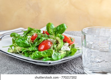 salad with avocado, mozzarella, Basil and cilantro in a beautiful plate stands on the table