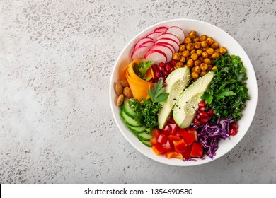 salad with avocado, roasted chickpeas, kale, cucumber, carrot, red cabbage, bell pepper and redish in white bowl, healthy vegan food, top view, copy space