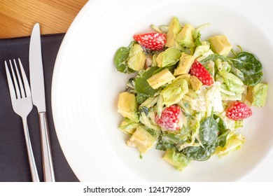 Salad with avocado, spinach and strawberries dressed with delicious sauce.