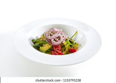 Salad with Avocado, Tomatoes and Onions on Flat Restaurant Plate Isolated on White Background. Healthy Vitamin Salat with Sliced Alligator Pear, Greens and Spices Close Up