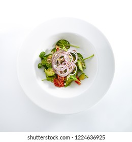 Salad with Avocado, Tomatoes and Onions on Flat Restaurant Plate Isolated on White Background. Healthy Vitamin Salat with Sliced Alligator Pear, Greens and Spices Top View