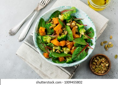 Salad with a baked pumpkin, chard, broccoli, and pumpkin seeds in ceramic plate on stone or concrete background table background. Selective focus. Rustic style. Top view. Copy space.
