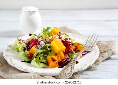 Salad with baked pumpkin on a plate, food