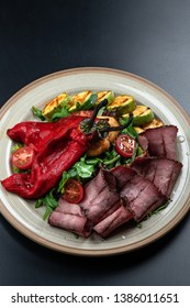 salad of baked vegetables with meat, top view black background