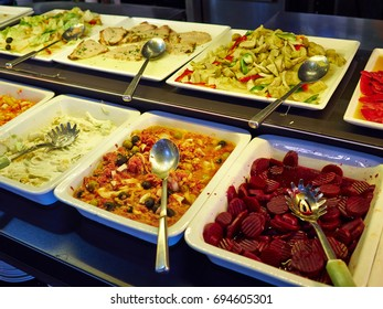 Salad bar with different fresh vegetables and other dishes in a hotel restaurant