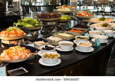 Salad bar and food in restaurant on black table.