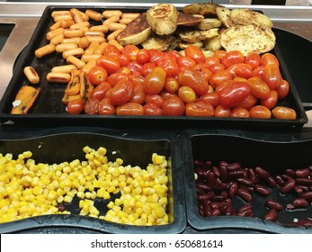 Salad bar with various fresh vegetables selection sweet corn, red peas, tomato, grill sausage and roasted potato in black tray, Selective focused with blur background
