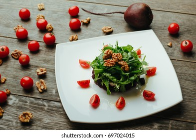 Salad with beet, cheese, cherry tomatoes, arugula and walnut on a plate on wooden background