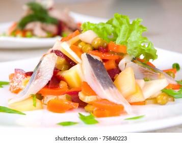 salad of beetroot, carrot, potato, green leek and herring