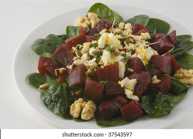 Salad with beets, boiled egg, and bean sprouts, walnuts on a bed of spinach