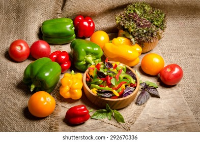 salad from bell pepper and basil in a wooden bowl and vegetables on wooden table