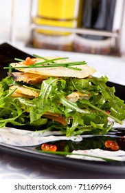 Salad in black plate closeup with fish