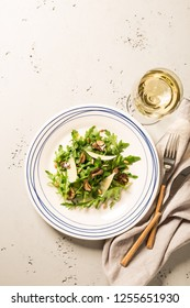 Salad with black truffles, arugula (rucola), parmesan cheese and sunflower seeds. Plate captured from above (top view, flat lay). Grey stone background. Layout with free text space.