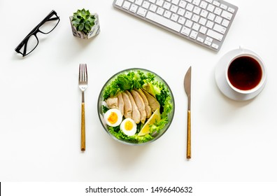 Salad bowl with healthy food on office desk with keyboard and tea on white background top view