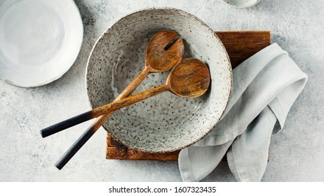Salad bowl with wooden salad spoon and fork. Top view.