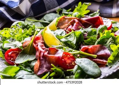 Salad bresaola arugula baby spinach tomatoes lime and cheese parmesan.