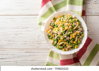 Salad with bulgur, green peas, corn, onion and greens on white rustic wooden table. Tabbouleh. Top view. Copy space.