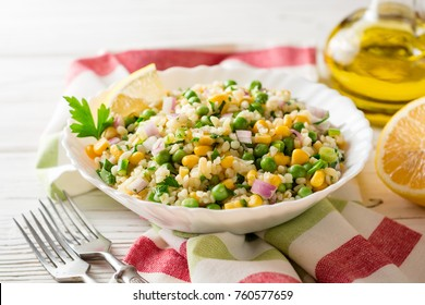 Salad with bulgur, green peas, corn, onion and greens on white rustic wooden table. Tabbouleh. Selective focus.