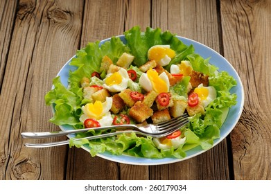 Salad Caesar with eggs, chili pepper and two forks