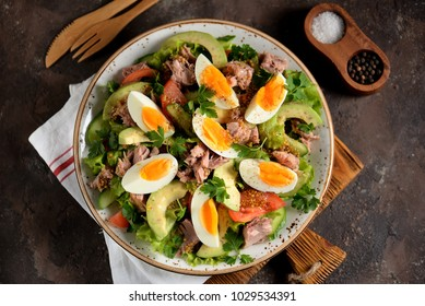 Salad with canned tuna, avocado, tomato, boiled egg, lettuce, parsley with olive oil dressing, lemon juice and grain mustard.