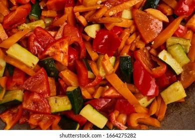 Salat mit Karotten, Paprika und Avocados. Salat mit Karotten, grüne und rote Paprika und Avocado in einem Wok. Koch bereitet einen Salat mit Karotten, grünen und roten Paprika und Avocados zu.