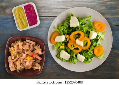 salad of cheese, lettuce, corn, pepper on a wooden background. Vegetarian salad on a plate. Vegetarian salad top view