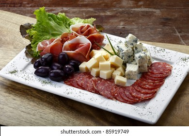 salad with cheese, olives, salami and parma ham