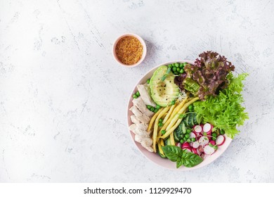 Salad with chicken breast with asparagus beans, radish, avocado, cucumber and lettuce on white background